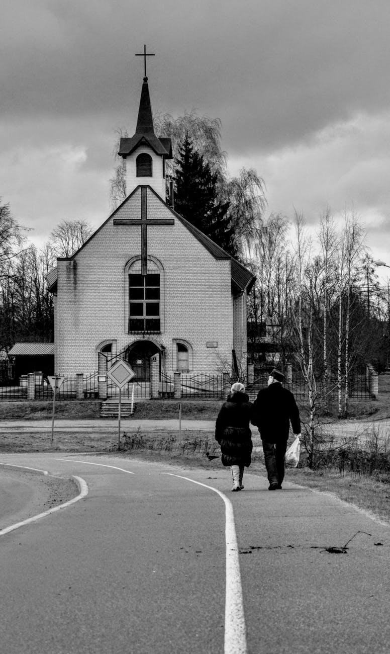 grayscale photo of man walking on sidewalk near church